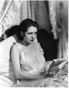 Billie Dove reading in bed c.1930.