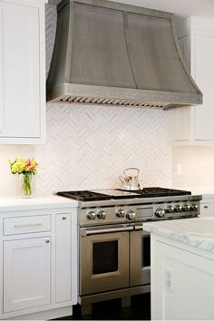 Gorgeous and simple herringbone tile pattern for a backsplash. I also love the range and venting system.