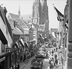 The people of Eindhoven line the streets of the town to watch British armoured vehicles pass through. The 101st US-Airborne Division had captured the town on the previous day.