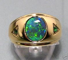 Mens Opal and Emerald ring in 14k Gold.  A design made previously but can be made to order.  Option available to change the accent stones to sapphire or diamonds etc.  Contact us with your inquiry for a no obligation quote.