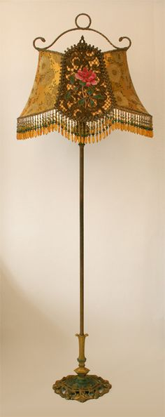 Ornate antique floor lamp with scrolls and roses holds a Golden Gate shade which is a copy of an antique lamp frame circa 1910-1920. Shade is covered in an antique golden Asian silk with metallic  threads and the center panel has a heavy bronze metallic lace overlaid with Chinese peony appliques and covered with a gossmer metallic mesh. HAnd beaded fringe in matching tones adorn the bottom.