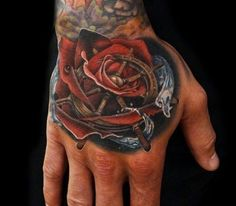 Rose and marine steering wheel tattoo on hand