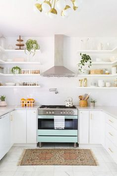 Feminine inspired kitchen with a retro chandelier, a mint oven, and a runner rug
