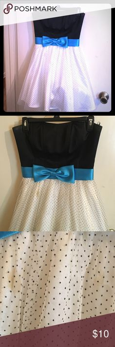 Cute Bow Tutu Style Dress Perfect for prom or any formal event, at flats and a cardigan for a more casual look. This dress has three layers, a tool lining underneath, a sheer polyester cloth on top, with a tool lining with black dots on top of that. The top half is black and is thick enough that you don't need a bra, and the waist line has a royal blue bow. There are two stains on the sheer lining, pictured above, but are hardly noticeable with the top tool. Dresses Strapless