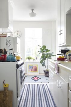 cute kitchen {white walls, cabinetry, and countertops, plus colorful area rugs}
