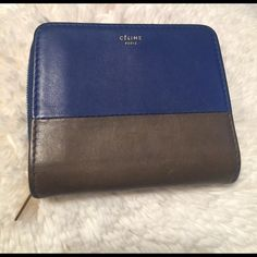 "Celine Bicolor Wallet in Blue/ Brown-Grey This wallet is incredibly functional, stylish, and is the perfect on-the-go piece!  The front is embossed with ""Celine Paris"" written in Gold lettering.  Very sleek and subtle.  It has multiple card slots, a bill pocket, and a built-in change purse with zip closure.  The zipper is an authentic RiRi zipper, which is very high quality. It is in great condition with no rips or tears.  It just has some light scratching and wear to the corners.  Get this…"