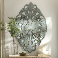 Use large wall decor to make a statement! The vintage blue and brushed gold accents of this Medallion Metal Plaque is beautiful and soothing.