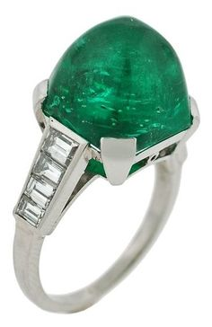 An Art Deco Cabochon Emerald, Diamond and Platinum Ring, 1920s. Centring a prong-set pyramidal cabochon emerald weighing approximately 14.77 carats, flanked by eight graduating Emerald-cut diamonds. #ArtDeco #ring