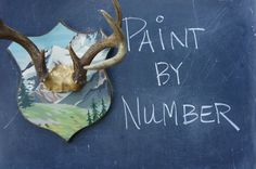A vintage paint by number picture was repurposed as a background for antlers. Upscale Downhome on Etsy