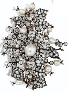 Pearl and Diamond Flower Brooch, French, circa 1850. Designed as a spray of flowers and leaves set throughout with numerous old-mine and rose-cut diamonds, altogether weighing approximately 30.00 carats, the central blossom set with a pearl measuring approximately 13.4 by 12.1 mm., further decorated throughout with 10 additional pearls of baroque and pear shape, mounted in gold and silver. #antique #brooch