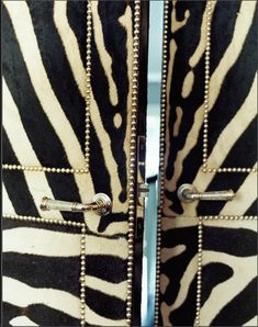 zebra upholstered doors with gold nailhead lining