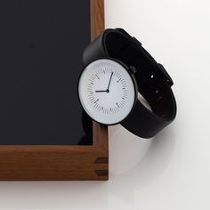 A contrasting white dial has markings close to the centre, leaving a clean outer band around the outside. Five minute increments are marked with a bold line and each quarter hour is numbered in a minimal typeface. Luxury Watches, Rolex Watches, Watches For Men, Dezeen Watch Store, Watch Brands, Clocks, Compact, Software, Minimal