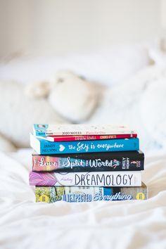 Foto de Melina Souza com livros empilhados em cima da cama branca.  Post com fotos dos livros que foram apresentados no Book Haul do mês de Junho.