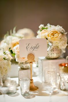 Table number   All white wedding ceremony with flowers in whites and nude colors, using Sahara roses, white ranunculus, white roses and white hydrangea   Yvette Roman Photography   Boutique Events LA   Tic Tock Couture Florals