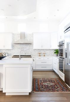 Modern kitchen with shell backsplash, a Persian area rug, and white cabinents