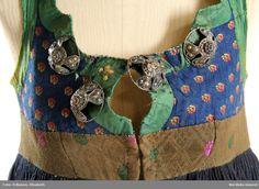 Livkjol med kjol av blåsvart  vadmal. 3 våder, den främre slät, bakvåderna goffrerade, helfodrad med blekt fintrådig linnelärft. Sprund mitt fram. Kort liv av halvsiden, blå mönstervävd  botten med  strödda stiliserade blommor liknande tassavtryck i gult och orange silke. 2 framstycken och 1 ryggstycke. Runt hals, ärmhål, framkanter och över nästan hela ryggen pålagda gröna sidenband 3 cm breda, på och runt banden broderi med silke i vitt, rosa, gult  och blått med plattsöm. och flätsöm…