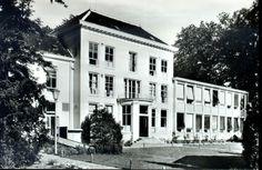 """Achterzijde van huize """"Zandhove"""",1965, gelegen aan de Hollewandsweg te Hoog-Zuthem. De aanbouw aan het hoofdgebouw is bij de laatste restauratie verwijderd. De buitenplaats Zandhove dateert uit de achttiende eeuw. Het was in bezit van vermogende Zwollenaren, rond 1800 kwam Zandhove in het bezit van de familie Van Naamen van Eemnes. Na de oorlog deed het huis dienst als Noodsanatorium en vanaf 1958 als verpleeghuis voor zieke en bejaarde Indische Nederlanders. Thans worden er bejaarden…"""