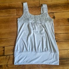 Light Grey loose fit tank w floral design on top Grey tank with thick straps, loose fit and tight on the bottom raised floral design on top, no size on tag, I would assume a medium but can provide measurements of needed, stretch material Drama Gold Tops Tank Tops