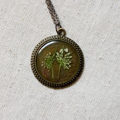 pressed flower necklace resin queen annes lace circle filigree edge in bronze real natural nature white wildflower botanical. $42.00, via Etsy.