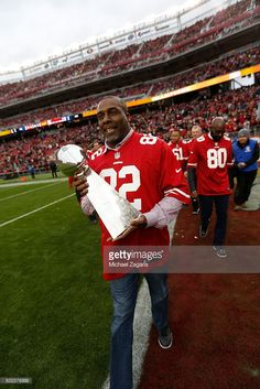 John Taylor stands on the field with a Super Bowl trophy during halftime of the game between the San Francisco 49ers and the Cincinnati Bengals at Levi Stadium on December 20, 2015 in Santa Clara, California.