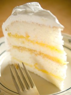 Lemon Rhapsody White Cake with Rich Lemon Filling and Fluffy White Frosting. Looks and sounds SO good.