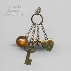From a designer's warehouse, a set of dangles from a jump ring.  Includes a key, a locket and a leaf all in brass plus a smooth amber glass bead.  This is vintage stock from the 1970's.  Top of jump ring to bottom of key, 42mm.  2 dangles.