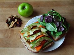 whole grain sandwich with hickory smoked tofurky, spinach, baby romaine, cucumber, carrot, avocado, hummus, and balsamic vinaigrette