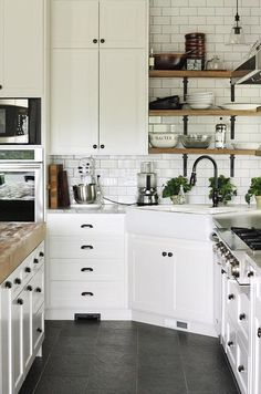 Farmhouse kitchen with cabinets painted in Benjamin Moore White Dove, white subway tile, a farmhouse sink and open wooden shelves | Lulu the Baker
