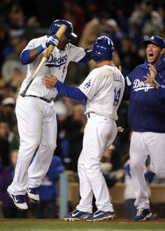 LOS ANGELES, CA - APRIL 13: Mark Ellis #14 of the Los Angeles Dodgers celebrates his game winning run with Juan Uribe #5 and Clayton Kershaw #22 off off a walk for a 9-8 win over the San Diego Padres during the ninth inning at Dodger Stadium on April 13, 2012 in Los Angeles, California. (Photo by Harry How/Getty Images)