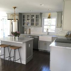 Gray kitchen features gray shaker cabinets adorned with brass pulls by Lewis Dolan paired with honed carrera marble countertops and a white mini subway tile backsplash.: