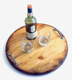 Especially handsome for presenting wine and cheese, this wood serving tray is styled like a barrel end. Each round tray is aged and stained to give it a charred, vintage look, and it's fitted with two metal handles for carrying. The rustic finish gives it a warm, inviting look, to make guests feel right at home.