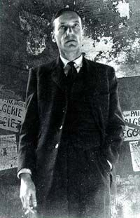 William Burroughs, Paris, 1959. Burroughs is wearing what he called his Rothschild suit. One of a number of images taken of Burroughs by Brion Gysin in the streets of Paris. Gysin told writer Terry Wilson that the series was an ironic magical operation intended to procure Burroughs' entry into the French Academy. Note the ripped, torn and detourned posters calling for a lasting peace agreement in Algiers, and the peeling upper walls in which the image of Africa serendipitously appears.
