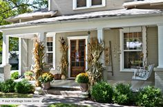 "Large corn stalks are definitely eye-catching as visitors approach this porch. A closer look also reveals endless beautiful details, such as hanging lanterns and a ""boo"" ladder, that are all cohesive thanks to their light and clean color palate.  See more at Our Vintage Home Love.    - CountryLiving.com"