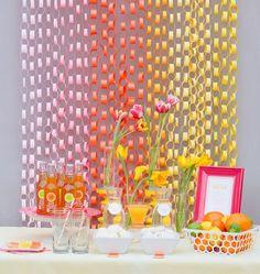Ideia simples e que dá um efeito muito bacana no fundo da mesa de doces - cortina com elos de papel colorido.