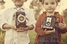Kids holding vintage cameras, by wild flowers photo