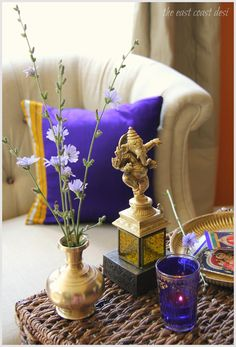 Chicory flowers, Brass Ganesha Statue and candles in a Moroccan tea glass