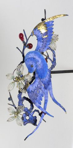 Hair ornament, Qing Dynasty (19th century), China, composed of gilded silver, silk thread, kingfisher feathers, pearls, glass beads, rubies. Likely once worn by the empress dowager, the effective ruler of China during the later years of the Qing Dynasty. It is an exquisite example of Chinese decoration and the symbolism used to express one's rank.