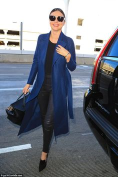 Putting in the leg work:  Miranda Kerr showed off her style credentials in a chic blue coat and sexy leather trousers as she turned heads at LAX airport on Friday