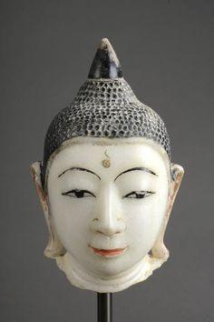 Tête de Buddha marqué de l'urna au milieu du front à la coiffure bouclée sommée d'un rasmi piriforme. Marbre blanc laqué et polychromé. Birmanie. Royaume d'Ava. 19 ème siècle. HT 26cm.