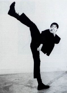 "Bruce Lee ""Demonstrate a hook kick."" While guarding upper head area and lower torso and groin area guards posture."