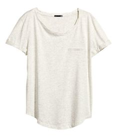 Top in soft slub jersey with slightly twisted neckline. Chest pocket, short sleeves with sewn cuffs, and rounded hem.