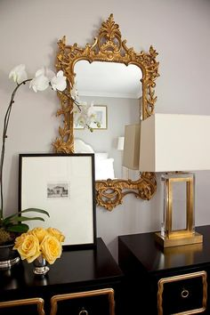 Exquisite bedroom features a pair of matching black and gold chests, Dorothy Draper style Espana Chests, placed side by side topped with yellow roses and a gold and lucite lamp situated under a gold baroque mirror.