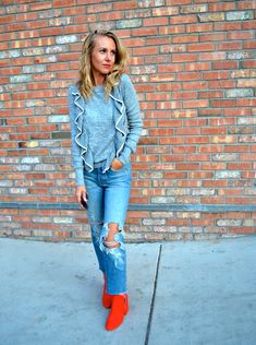 A Little Pop Of Red - Jaclyn De Leon Style- gray ruffle sweater +  distressed denim + red boots + casual fall style + chic winter outfit +  street style inspiration + fall booties + add red to your fall wardrobe