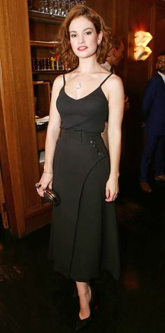 Lily James smoldered at the Downton Abbey wrap party in a black midi-length Dior skirt with button detailing on each side, styling it with a black cami, Monica Vinader jewelry, an Alexander McQueen clutch, and black pumps.