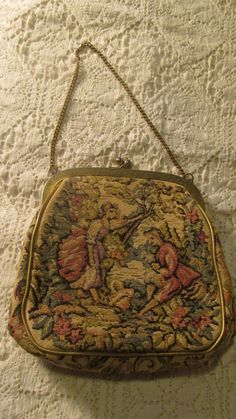"""Vintage Tapestry Purse Petit  Point Handbag Vintage JR of Florida Bag Metal Frame Purse Kiss Clasp Julius Resnick 1950s 50s    Vintage tapestry handbag is from Jr of Florida USA.  cream with pastels.  gold vinyl trim.  picture of a colonial period man and woman in a bucolic setterng.  gold metal frame and kiss clasp.  chain handle.  brown faille interior with no pockets.  Clean inside and out.  wear on frame.  please see all pictures.  circa 1950s   6"""" tall, 6"""" wide  1.5"""" deep  5.5"""" handle…"""