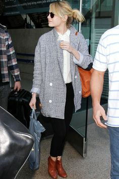 Traveling outfit: Black pants, white top, gray oversized cardigan and brown booties.