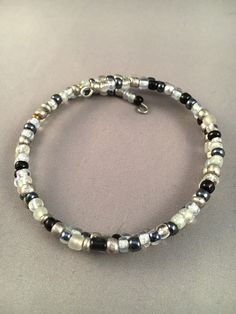 This is a memory wire bracelet of black, white and silver seed beads