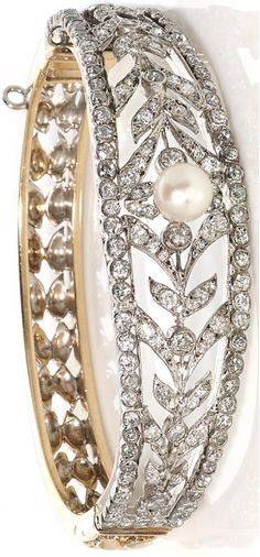A cultured pearl and diamond stylized foliate motif bangle bracelet; cultured pearl measuring approximately 7.1mm; estimated total diamond weight: 3.50 carats; mounted in silver-topped fourteen karat gold; diameter: 2 5/16in.