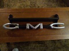 Grille from a 1960 to 1962 GMC truck.  Letters turned upsidedown on frame and then I added a shelf.  Triple Black paint.  Buffed the letters.