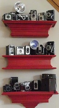 Vintage camera collection displayed on red shelves, (The owner acquired & painted the shelves for only 15 bucks.)